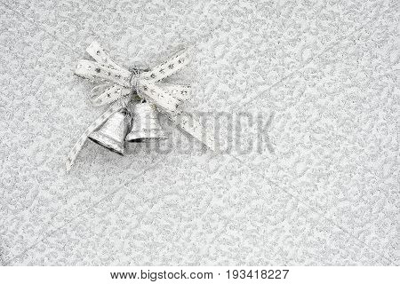 silver jingle bells on a silver background with copy space. conceptual christmas background.
