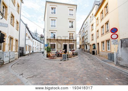 LUXEMBOURG, LUXEMBOURG - May 18, 2017: View on the Munster street with restaurant and people having a lunch in Grund district of the old town in Luxembourg