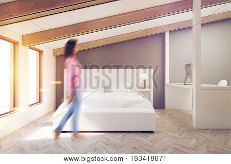 Woman in a gray attic bedroom with a wooden floor two large windows a white bed and a white table with a computer. 3d rendering mock up toned image
