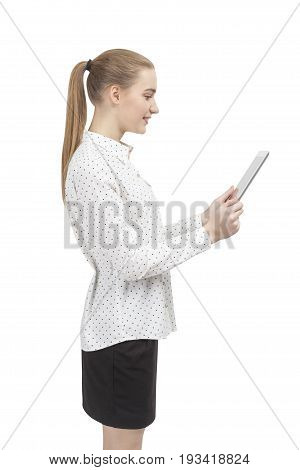 Side view of a blond businesswoman with a ponytail. She is wearing a white blouse and a black skirt and looking at a tablet computer she is holding with both hands. Isolated portrait