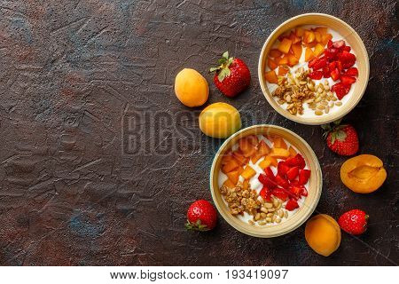 Natural yoghurt with pieces of apricots strawberries granola and pine nuts in two bowls on dark broun background. Top view with place for text