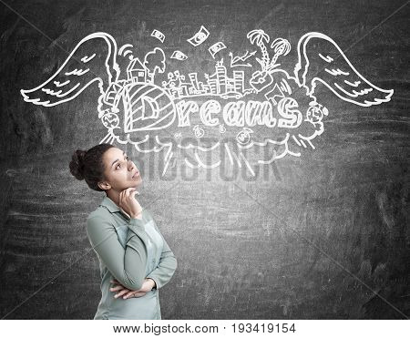 Side view of a beautiful African American woman standing near a chalkboard with a dream sketch drawn on it.
