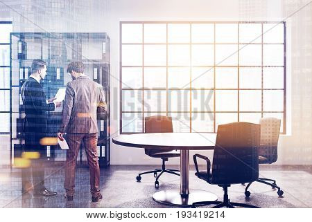 Men in a white loft office interior with a round table a bookcase with a number of binders white walls and a rectangular window with a square pattern 3d rendering mock up toned image double exposure
