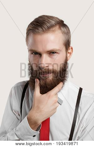 Style fashion and masculanity concept. Studio portrait of handsome fashionable young male with thick facial hair touching his fuzzy beard and looking at camera slightly squinting his eyes