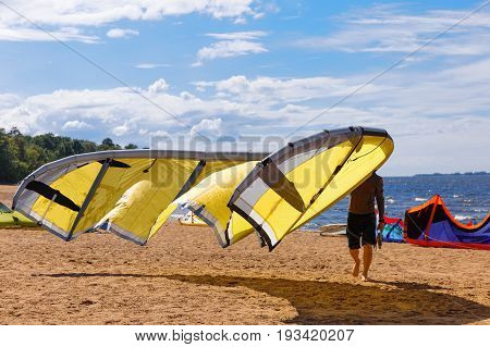 Kite surfer carries his yellow kite sunny day