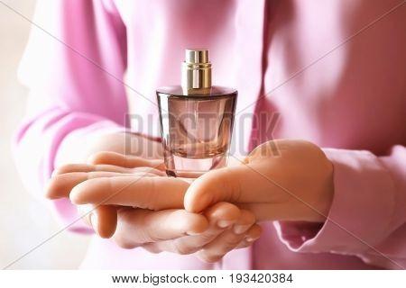 Female hands holding perfume bottle