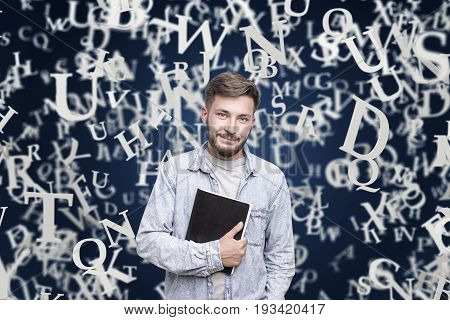 Portrait of a young bearded man in a jeans shirt holding a large black copybook and standing near a dark blue wall with white letters on it. Mock up
