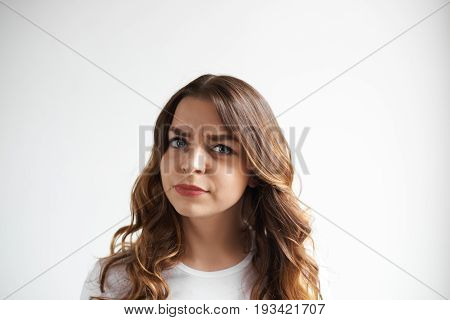 Serious beautiful young female wearing casual t-shirt feeling irritated and annoyed looking at camera frowning her eyes full of distrust disagreement and disappoinment. Human facial expressions