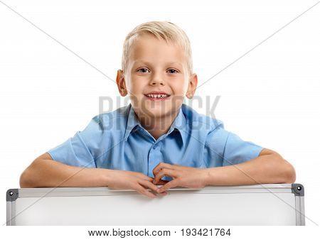 Portrait of cute schoolboy holding raised hand on whiteboard