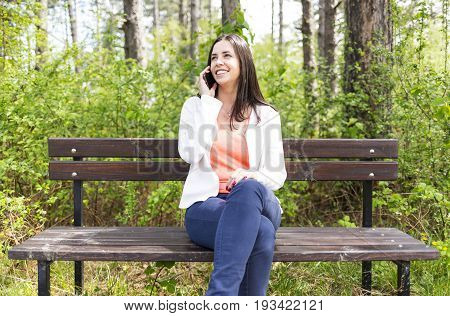 Attractive Smiling Young Woman With Smartphone In The Park