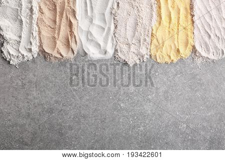 Composition with different types of flour on gray background