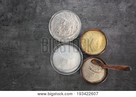 Bowls with different types of flour on gray background