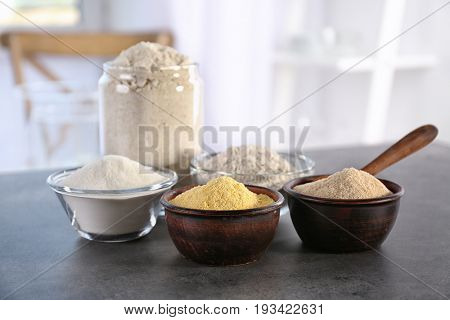Bowls with different types of flour on table