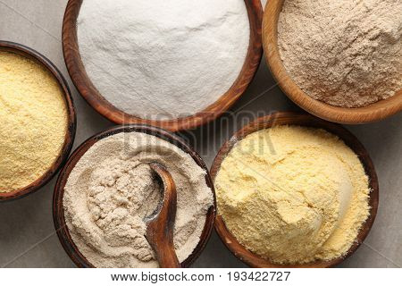 Wooden bowls with different types of flour on table, closeup