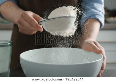 Human hands sifting flour into ceramic bowl, closeup