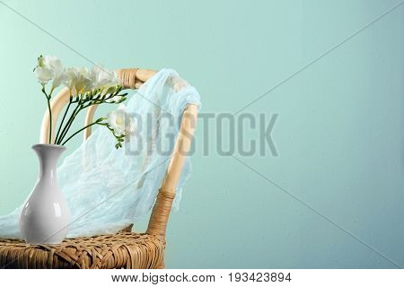 Vase with beautiful freesia on wicker chair against color background