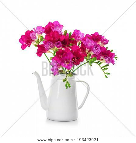 Beautiful bouquet of freesia in watering can on white background