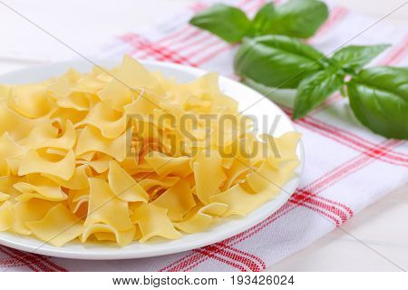 plate of quadretti - square shaped pasta on checkered dishtowel - close up