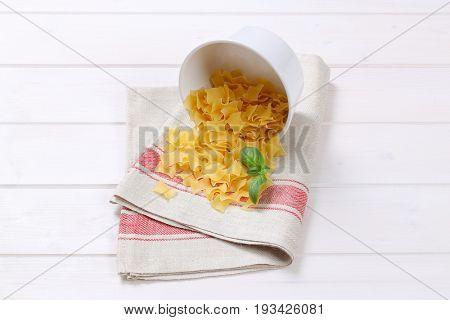bowl of quadretti - square shaped pasta spilt out on place mat