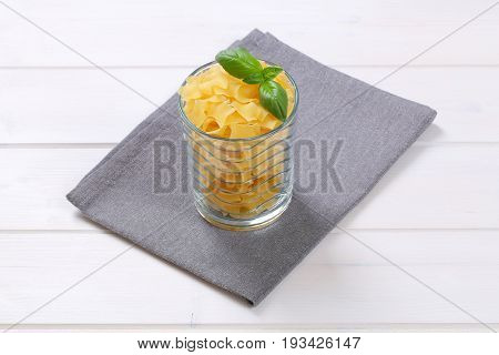 glass of quadretti - square shaped pasta on grey place mat