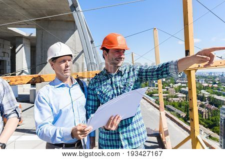 Two Builders On Construction Site Looking At Plans Contractor Meeting With Business Man Discussing Project Outdoors
