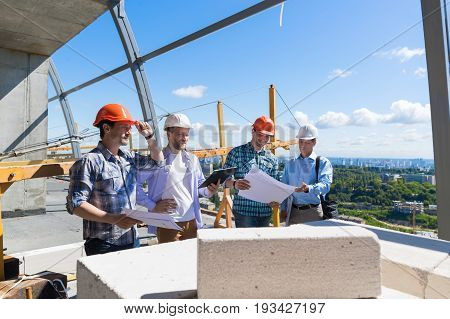 Group Of Builders On Construction Site Building Team Of Apprentices Meeting With Contractor Review Project Plan Outdoors