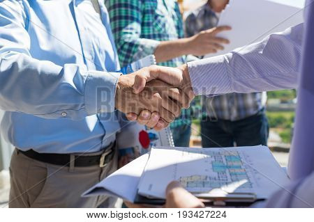 Builders Handshake Closeup, Two Building Business Men Making Deal After Discussion Of Blueprint To New Project With Foreman Team On Site