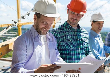 Architect And Builders Looking At Buiding Plan Blueprint Wearing Hardhat While Meeting On Construction Site, Team Of Engineers Communication