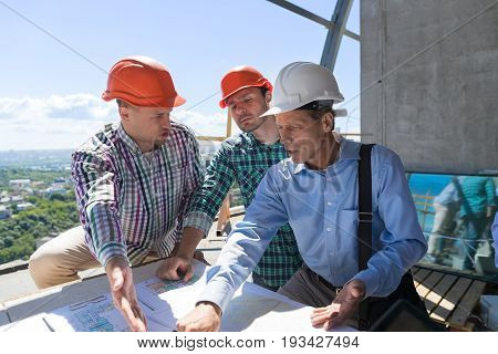 Team Of Builders Working With Blueprint On Site Architect Explain Construction Plan To Team Og Engineers During Foreman Meeting