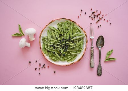 Dry green foglie pasta made from durum wheat semolina dried tomatoes spinach and water. Top view on vintage plate and old silver cutlery with champignons and pepper on pink background