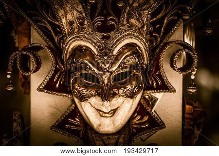 Elegant Venetian Carnival Mask Closeup Photo. Dark Golden Sepia Color Grading. Commedia Dell'arte.