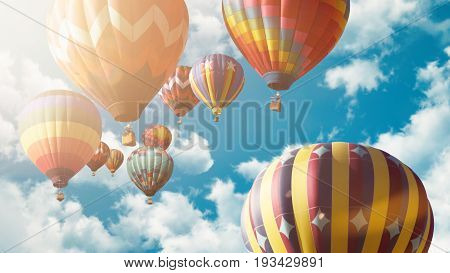 Colorful hot air balloons in front of blue sky with clouds and sunshine