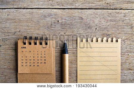 June. Calendar sheet. Two thousand seventeen year calendar pen and list of paper on wooden background.