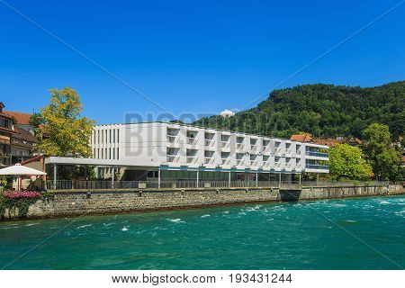 Thun, Switzerland - 21 July, 2015: buildings along the Aare river in the city of Thun in summer. Thun is a city and municipality in the administrative district of Thun in the Swiss canton of Bern, located where the Aare river flows out of Lake Thun.