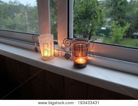 Two candles burning on the windowsill in deep candle holders.