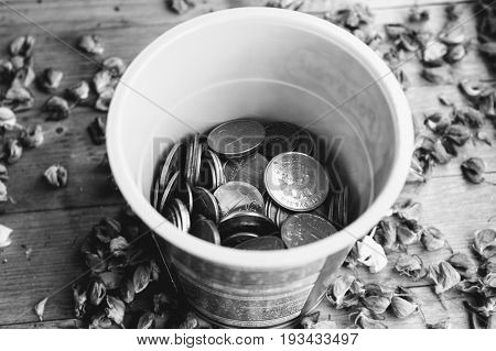 Box of coins (Russian rubles) stands on a wooden table. Black and white version.