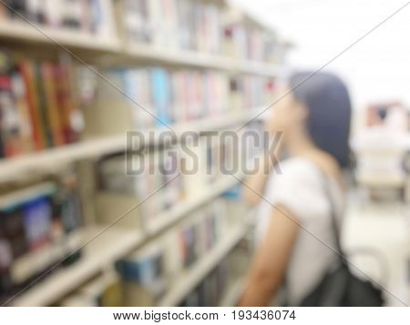 Blurred Image Of Woman Student Walking To Search And Take A Book At Bookshelves In Book Store. Stude