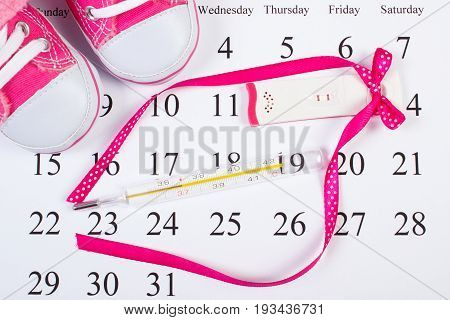 Pregnancy Test With Positive Result, Thermometer And Baby Shoes On Calendar