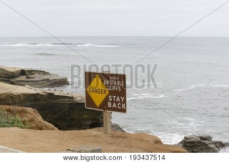 Danger sign warning of sheer cliffs as result of erosion by ocean