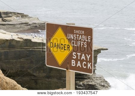 Danger sign warning of sheer cliffs as result of erosion by Pacific Ocean