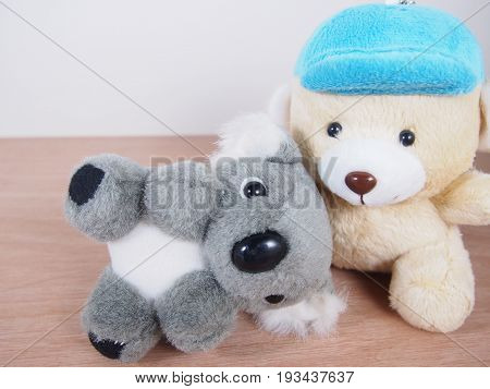 Little gray koala bear doll lie down on light beige bear's lap wood floor