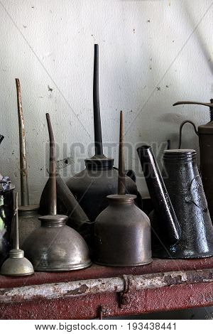 A collection of grungy antique oil cans on a red shelf.