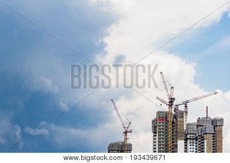 Highrise tower crane and new unfinished residential townhouse under construction buildings front view. Urban development theme. Blue sky and cloud background.
