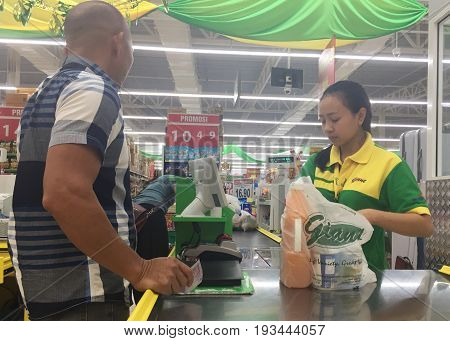 Keningau,Sabah-June 23,2017:Customer make payment for buying goods with cash in the counter of Giant Malaysian Supermarket in Keningau,Sabah.Giant,pioneered the concept of modern supermarket shopping.