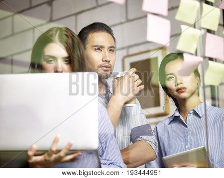 a team of asian business people conducting a SWOT analysis in office using laptop computer and sticky notes.