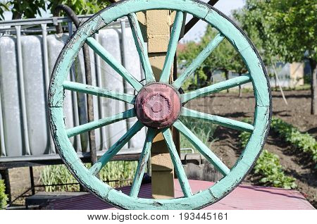 Green wooden cart wheel and green background