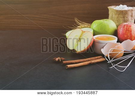Bakery background comprise with apples wheat flour egg and cinnamon on granite table with copy space.Prepare ingredient for baking apple cake on granite background. Bakery background concept. Ingredients of apple cake for bakery background.
