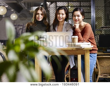 three female entrepreneur asian and caucasian looking at camera smiling while working in office.