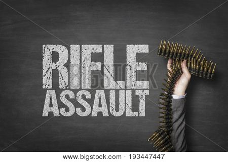 Cropped hand of businessman holding bullets with rifle assault text on blackboard