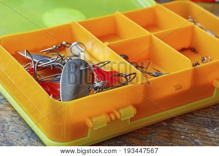 Metal Fishing Baits In A Orange Plastic Storage Box Closeup
